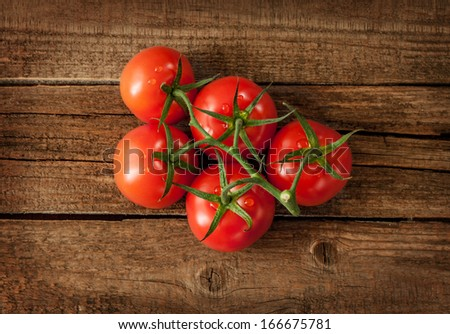 Tomato branch on vintage wood table - rural still life from above, fresh harvest from garden - stock photo