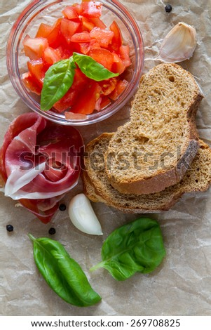 Tomato bruschetta with basil leafs, garlic, meat, cottage cheese on baking paper, rustic wood background, top view