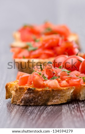 Tomato Bruschetta with olive oil, garlic and fresh basil leaves - stock photo