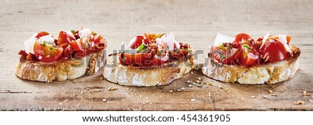 Tomato bruschetta with parmesan cheese served on toasted slices of baguette for a traditional Italian appetizer, panoramic banner format - stock photo