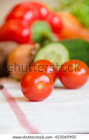 tomato cherry vegetables cucumber, carrots, potatoes, peppers, onions, basil, pepper on a white tablecloth - stock photo