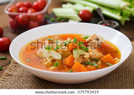 Tomato chicken soup with pumpkin, beans and celery in white bowl