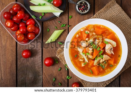 Tomato chicken soup with pumpkin, beans and celery in white bowl. Top view