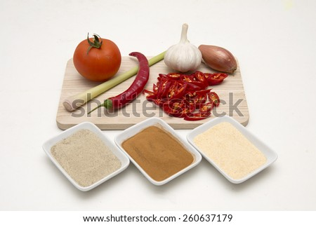 Tomato, chili peppers, garlic, onion, lemongrass, and powder kitchen herbs isolated on white background - stock photo