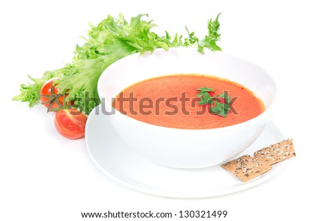 Tomato cream soup garnished with salad leaves and crispbread on a white background - stock photo