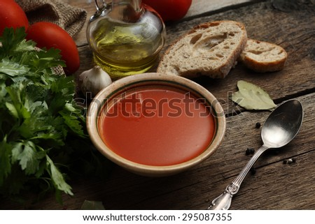 Tomato cream soup with ingredients on wooden background.  - stock photo