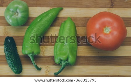 Tomato, cucumber and pepper on the kitchen desk - stock photo