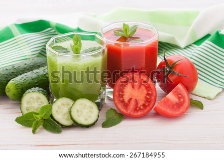 Tomato, cucumber Juices and vegetables on white wooden table - stock photo