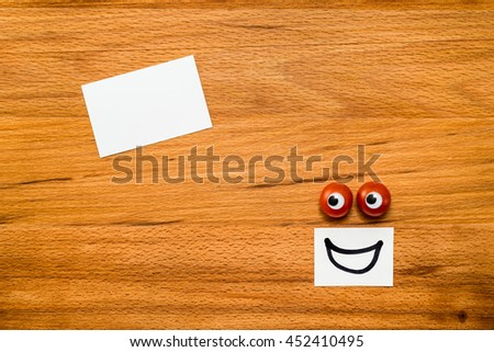 Tomato eyes smiling and looking at blank card on wooden table. Close-up view from above - stock photo