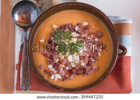 Tomato gazpacho soup in a ceramic bowl with the raw ingredients, tomatoes, eggs, oil and bread over white background - stock photo