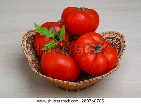 Tomato in the basket with fresh green branch - stock photo