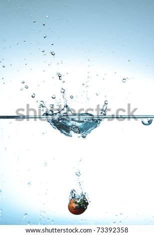 Tomato into water drip - stock photo