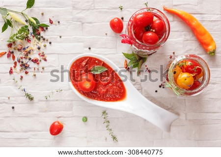 Tomato jam. Spicy tomato jam  on spoon and fresh tomatoes in a glass jar, top view - stock photo