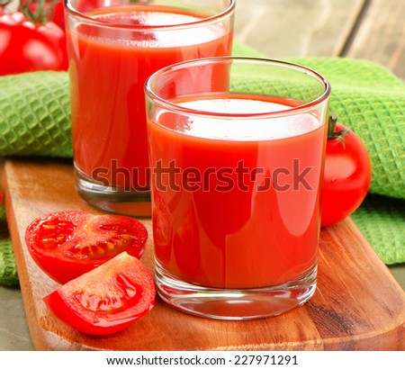 Tomato juice and ripe tomatoes  on  a wooden background. Selective focus