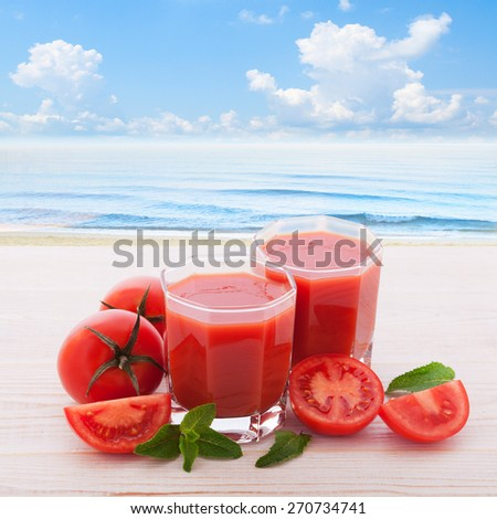 Tomato juice and vegetables on white wooden desk. Panorama of tropical landscape sky, sea, beach - stock photo