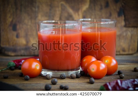 tomato juice cherry on a brown wooden background with pepper and cherry - stock photo