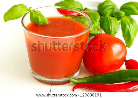 Tomato juice, chili pepper and basil leaf on white wooden background