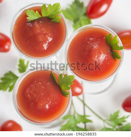 Tomato juice cocktails garnished with parsley leaves on a white wooden background and cherry tomatoes - stock photo