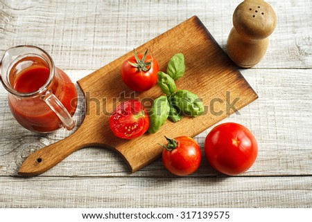 Tomato juice in a glass jug on the wooden table - stock photo