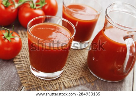 Tomato juice in a glass on a wooden table