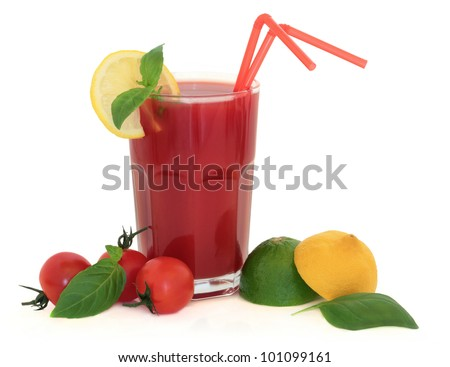 Tomato juice in a glass with lemon, lime, tomatoes and basil herb leaf over white background.