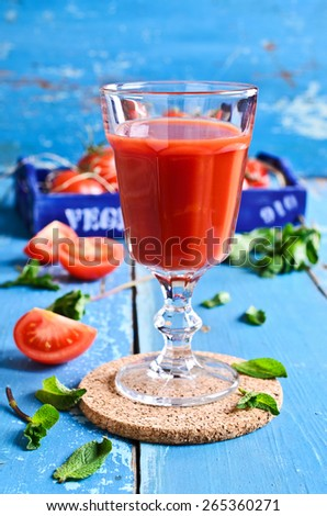 Tomato juice in a glass with mint leaves on the background of the box of tomatoes on a wooden surface - stock photo
