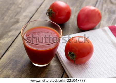 Tomato juice in glass and fresh tomatoes on vintage wooden table - stock photo