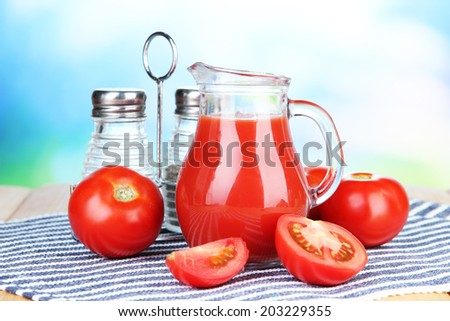 Tomato juice in glass jug, on wooden  table, on bright background - stock photo