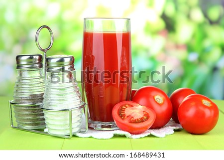 Tomato juice in glass, on wooden  table, on bright background - stock photo