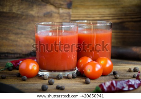 tomato juice pepper on a brown wooden background with pepper and cherry - stock photo