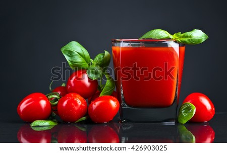 tomato juice with basil on black table