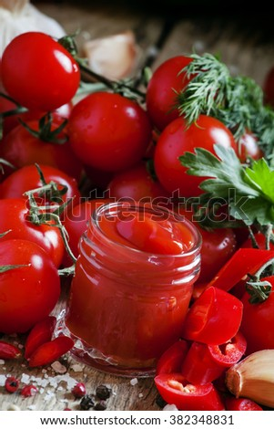 Tomato ketchup hot sauce with chili pepper and cherry tomatoes in a small glass jar, selective focus - stock photo