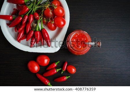 Tomato ketchup sauce with cherry tomatoes and mini red hot chili peppers in a small glass jar with a spoon on dark wooden background. Homemade tomato sauce and fresh tomatoes. Top view. Copy space. - stock photo