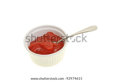 Tomato ketchup with a spoon in a ramekin isolated against white