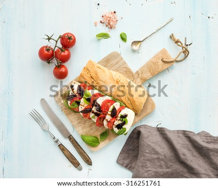 Tomato, mozzarella and basil sandwich on wooden chopping board over light blue background, top view - stock photo