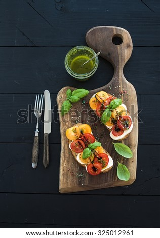 Tomato, mozzarella and basil sandwiches on dark wooden chopping board, pesto jar, dinnerware over black background, top view. - stock photo