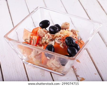 Tomato, olives and tuna in salad in a glass, horizontal image - stock photo