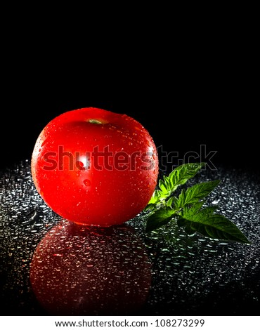 tomato on black background - stock photo