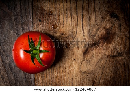 tomato on brown textured wood - stock photo