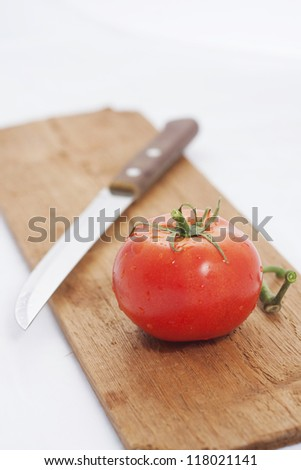 tomato on the wood board with knife