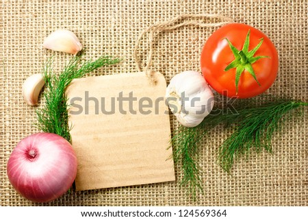 tomato, onion and garlic with cardboard price tag on sacking background