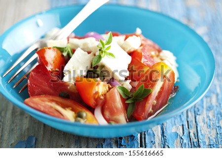 tomato,onion,feta salad sprinkled with fresh basil, capers and virgin olive oil - stock photo