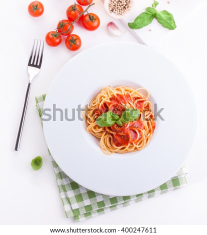 Tomato pasta spaghetti with fresh tomatoes, basil, italian herbs and olive oil in a white bowl on a white wooden background, top view  - stock photo