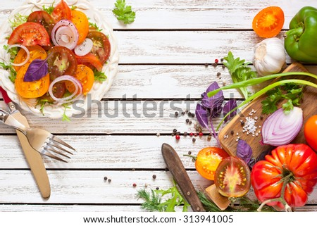 Tomato salad and fresh vegetables and herbs for cooking. - stock photo