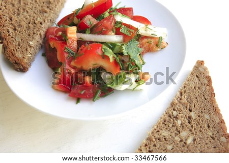 tomato salad and rye bread on white table
