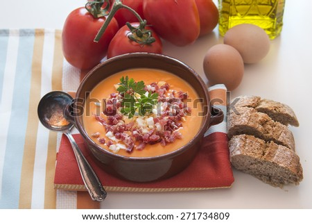 Tomato salmorejo soup in a ceramic bowl with the raw ingredients, tomatoes, eggs, oil and bread over white background - stock photo