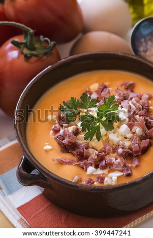 Tomato salmorejo soup in a ceramic bowl with the raw ingredients, tomatoes, eggs, oil and bread over white background