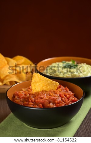 Tomato salsa with a nacho in it and guacamole sauce in the back (Selective Focus, Focus on the nacho in the tomato salsa) - stock photo