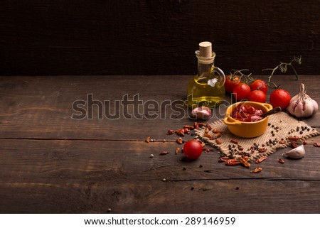 tomato sauce and ingredients over dark wooden table