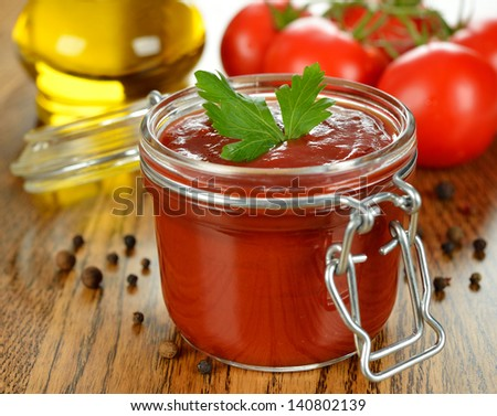 Tomato sauce in a glass jar on a brown table - stock photo